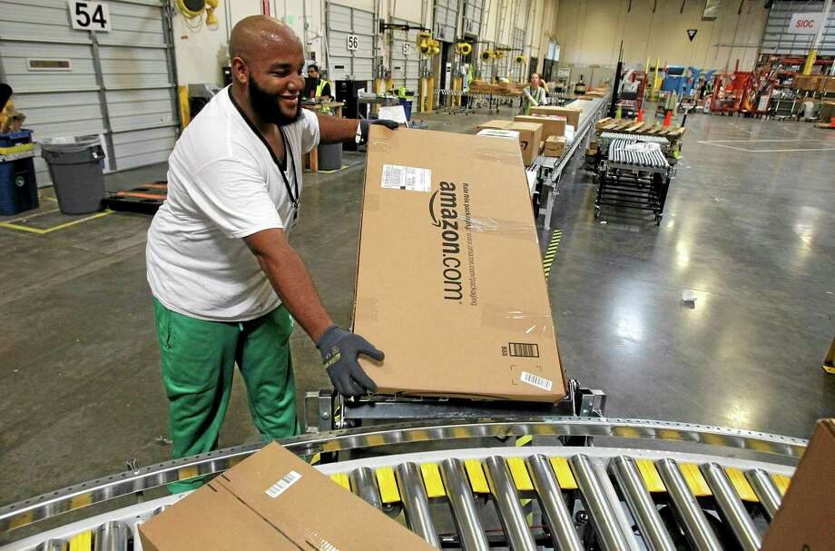 Leacroft Green places a package to the correct shipping area at an Amazon.com fulfillment center, in Goodyear, Ariz. Amazon is teaming up with the U.S. Postal Service to deliver packages on Sundays. Photo: Ross D. Franklin — The Associated Press File Photo   / AP