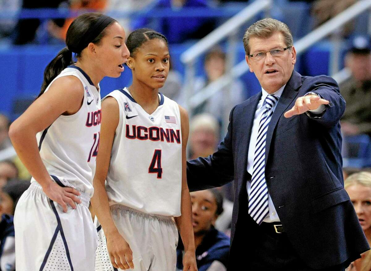 UConn coach Geno Auriemma speaks with guards Bria Hartley (14) and Moriah Jefferson (4) during the first half of Saturday's game against Hartford.