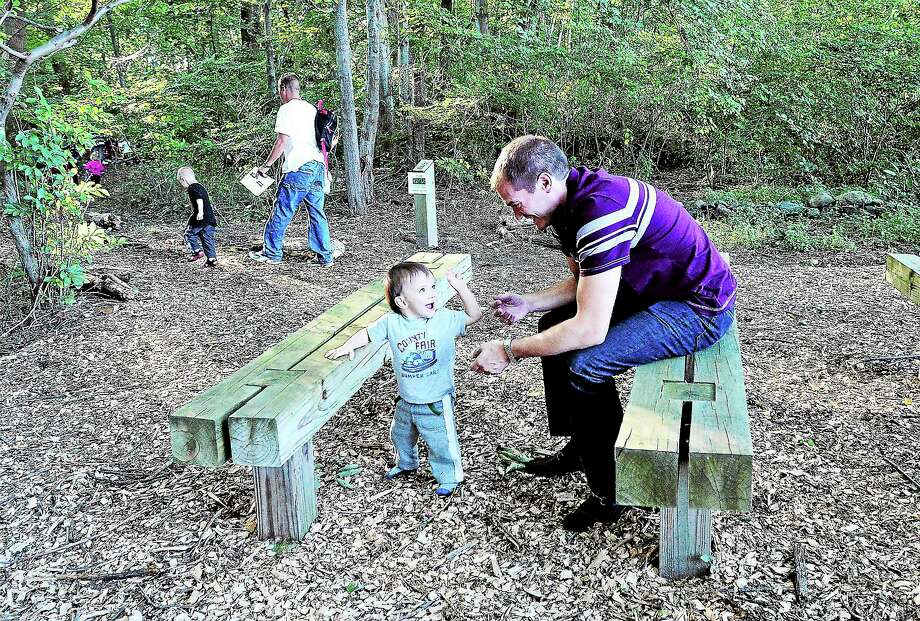 Cengiz Zanbak and his son, Cyrus, 1, sit in the new outdoor classroom at the Orange Avenue School in Milford moments after a ribbon-cutting for the new trail and outdoor learning center at the school Friday. Photo: (Peter Casolino — New Haven Register)