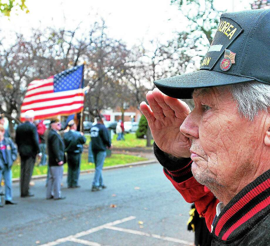 (Peter Casolino — New Haven Register) John Phillips Sr., 86, a WWII and Korea Marine veteran, salutes as the flag passes along Broad Street during the Milford Veterans Day Parade November 10, 2013. pcasolino@NewHavenRegister Photo: Journal Register Co.