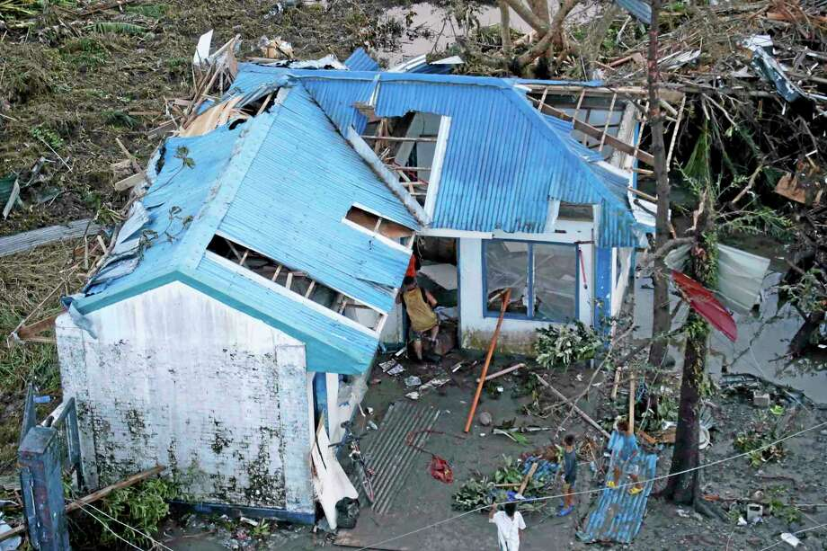 """Residents sift through the rubble of their damaged house following a powerful typhoon that hit Tacloban city, in Leyte province, central Philippines Saturday, Nov. 9, 2013. The central Philippine city of Tacloban was in ruins Saturday, a day after being ravaged by Typhoon Haiyan, one of the strongest typhoons on record, as horrified residents spoke of storm surges as high as trees and authorities said they were expecting a """"very high number of fatalities."""" (AP Photo/Bullit Marquez) Photo: AP / AP"""