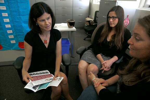 UCSF director for women centered contraception Dr. Christine Dehlendorf (left) talks with project managers Whitney Wilson (middle) and Reiley Reed (right) about teen pregnancy intervention materials on Friday, July 21, 2017, in San Francisco, Calif.  The UCSF program will be loosing $2.8 million federal funding of the $213.6 million awarded by the Obama administration to find scientifically valid ways to help teenagers avoid pregnancy.