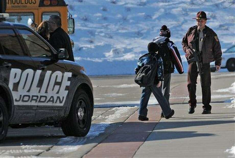 """A Minnesota State Patrol officer escorts students into New Prague Middle School in New Prague, Minn., Wednesday, March 20, 2013 after authorities in New Prague responded to a 911 call concerning an """"active shooter"""" at the middle school, but a staff member later said everyone is safe and there is no danger inside the building. The 911 call in which a caller claimed several people had been gunned down at the school was likely a hoax, Scott County Sheriff Kevin Studnicka said said Wednesday. (AP Photo/The Star Tribune, Richard Sennott) Photo: AP / The Star Tribune"""