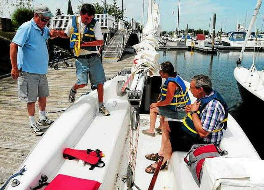 Robert Rackliff of Madison, the Director of Operations at Sail Connecticut Access, left, assists Jonathan Recor of Westbrook, 48, unto a Catalina Independence 20 sailboat at the Brewer's Bruce & Johnson Marina in Westbrook Wednesday, July 3, 2013. Recor, who as a park ranger in Rhode Island was seriously beaten, has a Traumatic Brain Injury. In the boat is case manager Georgette Holmes with her client George Sarantis of Bridgeport, who was in the merchant marine and was a recreational sailor before getting a traumatic brain injury, far right. Sail Connecticut Access gets people with disabilities on on the water and sailing, which serves as an emotionally therapeutic outlet. Peter Hvizdak -- Register
