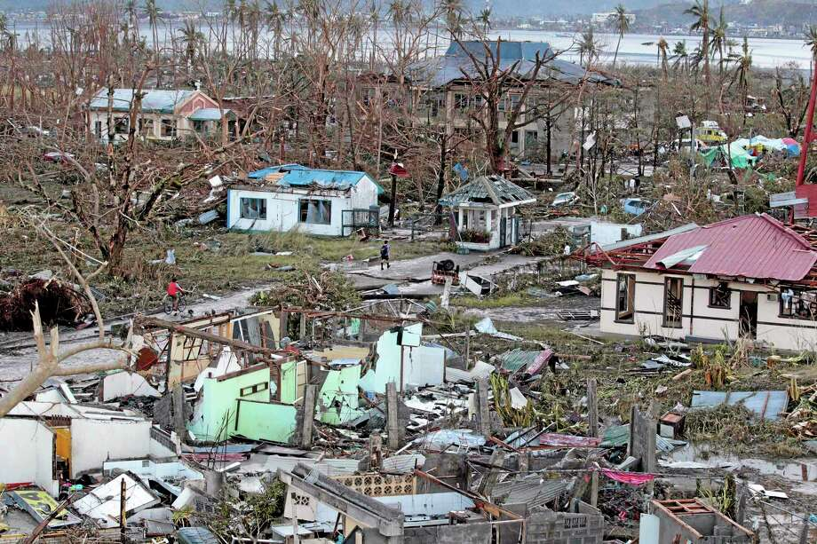 A resident walks by remains of houses after powerful Typhoon Haiyan slammed into Tacloban city, Leyte province central Philippines on Saturday, Nov. 9, 2013. Rescuers in the central Philippines counted at least 100 people dead and many more injured Saturday, a day after one of the most powerful typhoons on record ripped through the region, wiping away buildings and leveling seaside homes with massive storm surges. (AP Photo/Aaron Favila) Photo: AP / AP