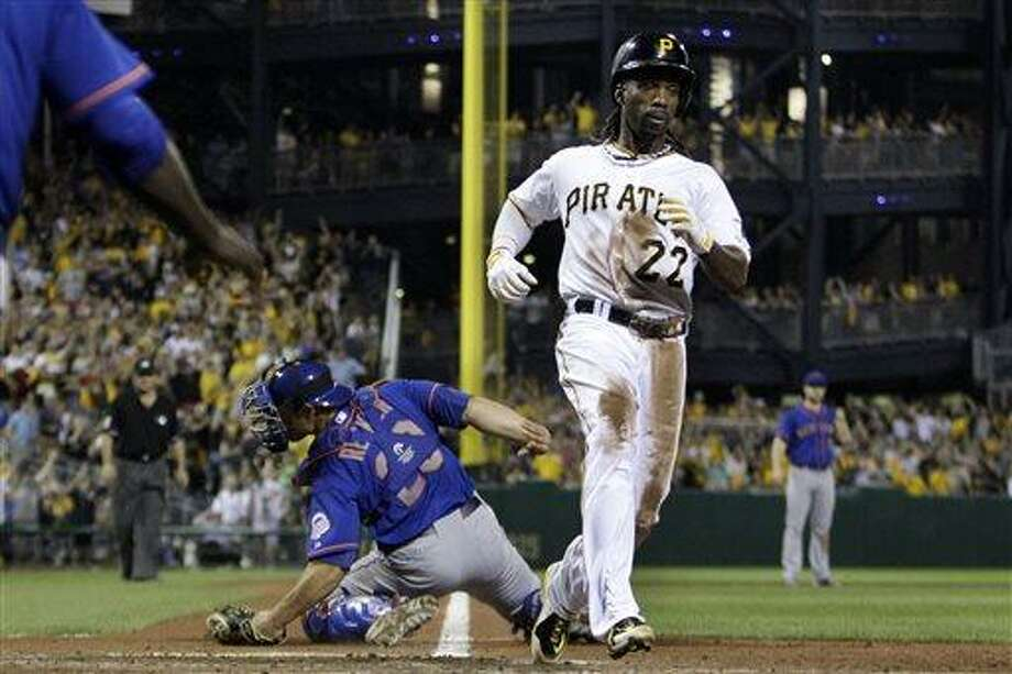 Pittsburgh Pirates' Andrew McCutchen (22) scores the game-winning run past New York Mets catcher Anthony Recker on a single by Jordy Mercer in the 11th inning of a baseball game in Pittsburgh Friday, July 12, 2013. The Pirates won 3-2. (AP Photo/Gene J. Puskar) Photo: AP / AP