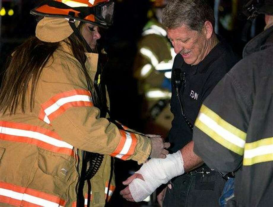 An FDNY firefighter is treated for an arm injury at the scene of the rescue of a trapped worker at an MTA subway construction project in New York  Tuesday, March 19, 2013. The worker was rescued early Wednesday morning after being trapped up to his chest in debris for several hours. (AP Photo/Craig Ruttle) Photo: AP / FR61802 AP