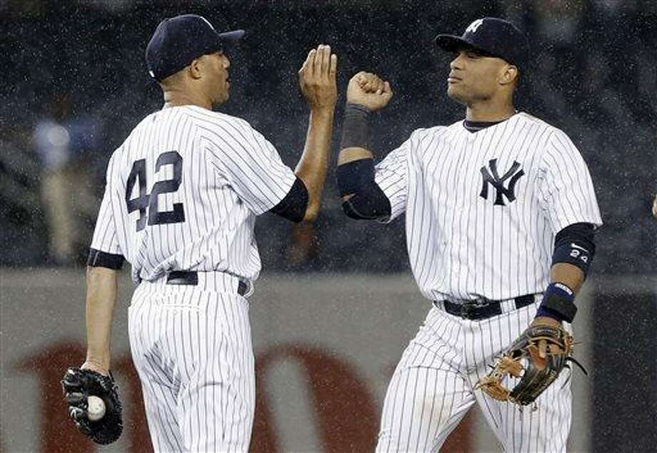 New York Yankees' Mariano Rivera (42) and Robinson Cano (24) celebrate after a baseball game against the Minnesota Twins on Friday, July 12, 2013, in New York. The Yankees won 2-0. (AP Photo/Frank Franklin II) Photo: AP / AP