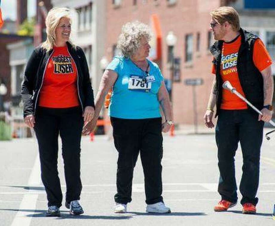 "Jackie and Dan Evans (both in red) who lost a combined 225 pounds on the TV show ""The Biggest Loser,"" are participating in the show's RunWalk race series across the country. (The Biggest Loser RunWalk) Photo: THE WASHINGTON POST / THE WASHINGTON POST"