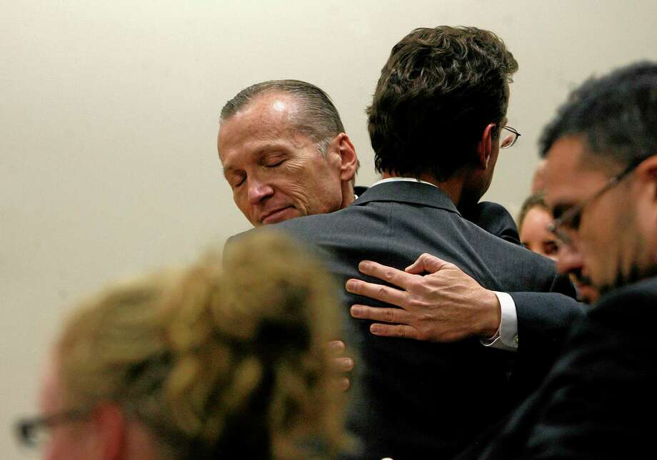 Martin MacNeill hugs attorney Randy Spencer as he thanks his defense team after he was found guilty of murder and obstruction of justice early Saturday morning, Nov. 9, 2013. He faces 15 years to life for first-degree murder when he is sentenced Jan. 7. He also was found guilty of obstruction of justice, which could add 1-15 years. MacNeill was led by deputies back to Utah County jail. (AP Photo/The Salt Lake Tribune, Scott Sommerdorf) Photo: AP / The Salt Lake Tribune 2013