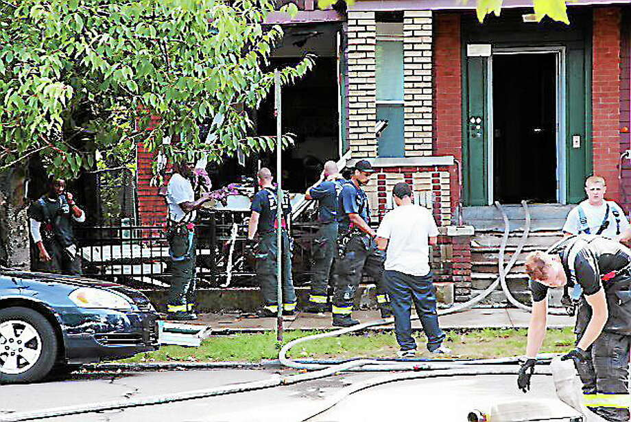 Firefighters overhaul a fire scene at Elm Street Thursday. Photo by Rich Scinto/ New Haven Register. Photo: Journal Register Co.
