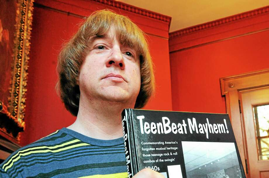 "Mike Markesich, author of ""Teen Beat Mayhem!"" poses with his book at the James Blackstone Memorial Library in Branford  . Photo: VM Williams — New Haven Register"