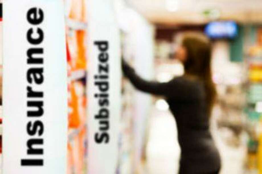 """Woman reaches for something in a supermarket's toiletries aisle. Focus is on the big sign on the left that says """"diapers"""". Camera: Canon EOS 1Ds Mark III."""