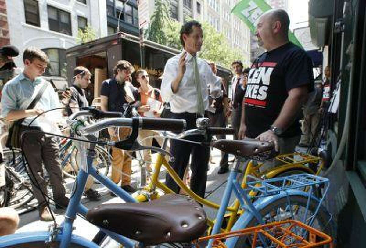 New York mayoral candidate Anthony Weiner, center, meets with John Keoshgerian, right, owner of Zen Bikes, in New York, Monday, July 8, 2013. Weiner is supporting a tax break for employers to encourage employees to bike to work. (AP Photo/Mark Lennihan)