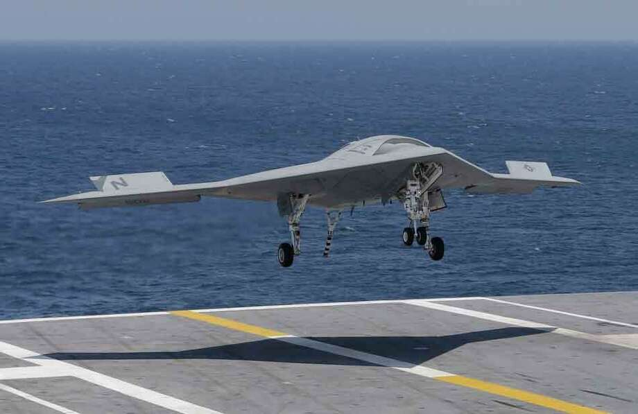 A X47-B Navy drone approaches the deck as it lands aboard the nuclear aircraft carrier USS George H. W. Bush off the Coast of Virginia Wednesday, July 10, 2013. It is the first landing by a drone on a Navy carrier.  (AP Photo/Steve Helber) Photo: ASSOCIATED PRESS / AP2013