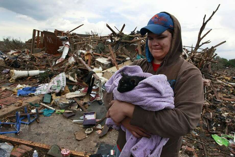 Austin Brock holds cat Tutti, shortly after the animal was retrieved from the rubble of Brock's home, which was demolished a day earlier when a tornado moved through Moore, Okla., Tuesday, May 21, 2013. A huge tornado roared through the Oklahoma City suburb Monday, flattening an entire neighborhoods and destroying an elementary school with a direct blow as children and teachers huddled against winds. (AP Photo/Brennan Linsley) Photo: AP / AP