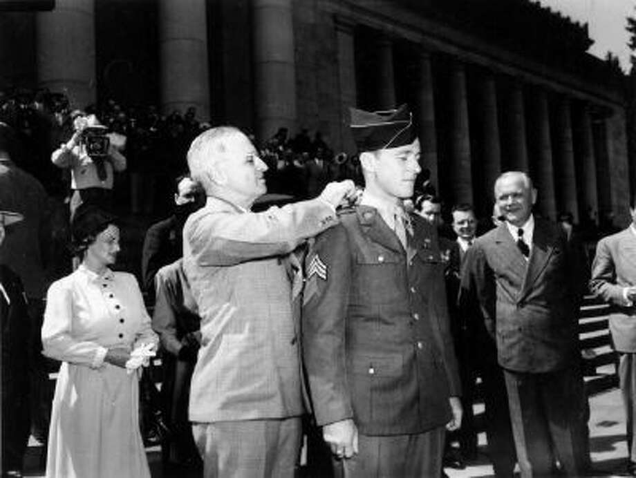 June 24, 1945. President Truman presents a Congressional Medal of Honor to Sgt. John D. Hawk at Olympia, Washington.