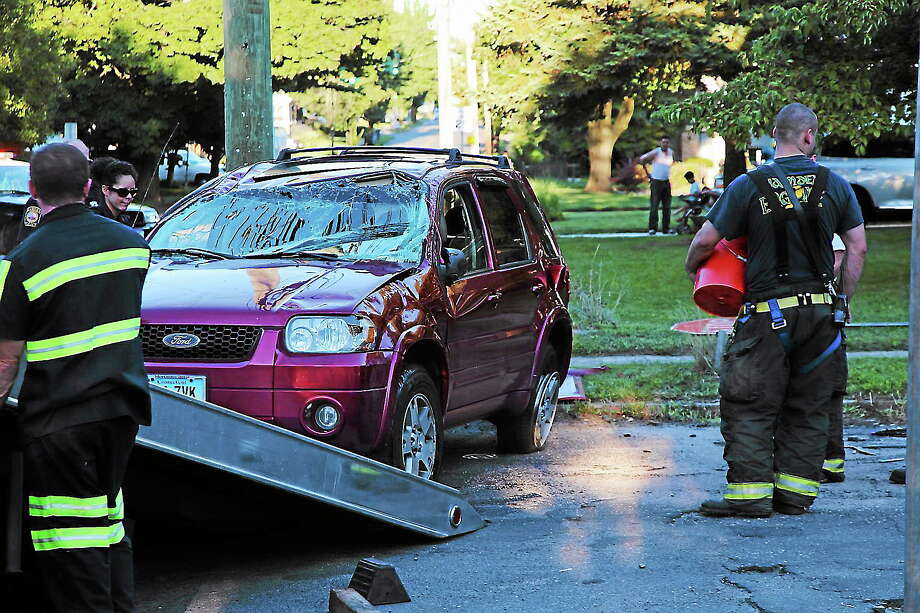 Firefighters put material down to soak up liquids following a two-vehicle accident at the intersection of Woodin Street and Sunset Road in Hamden. Photo by Rich Scinto/ New Haven Register. Photo: Journal Register Co.