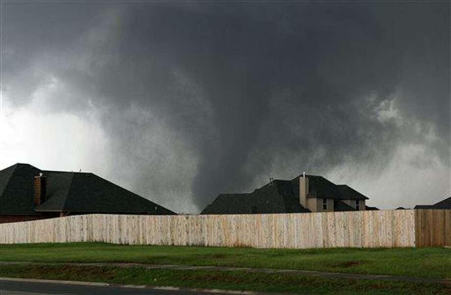 A tornado moves past homes in Moore, Okla. on Monday, May 20, 2013. (AP Photo/Alonzo Adams) Photo: AP / FR159426 AP