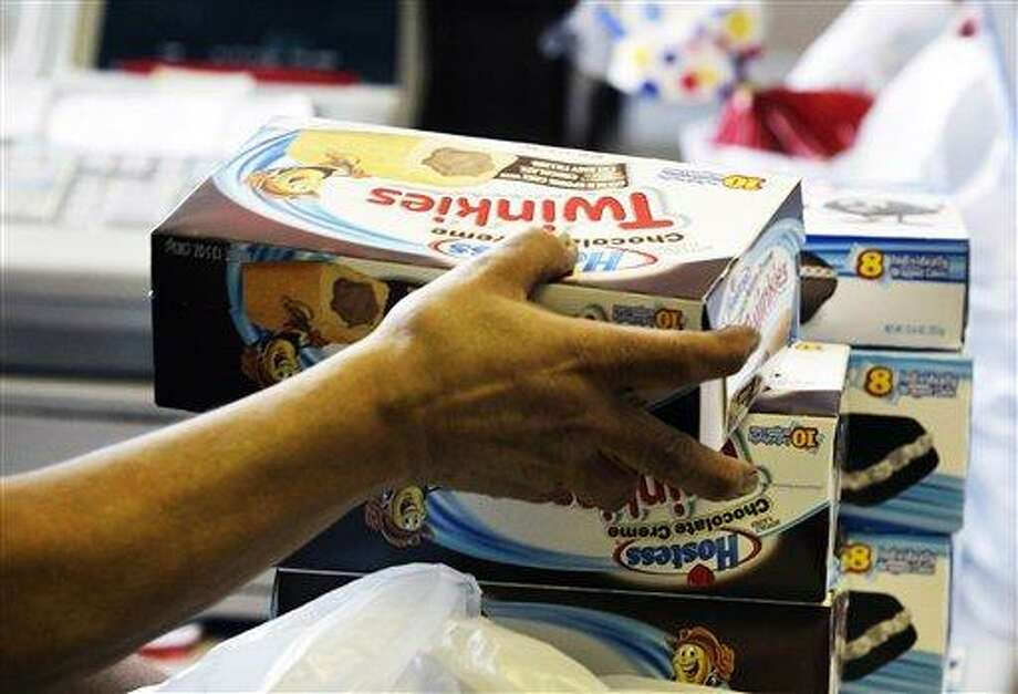 FILE - In this Nov. 16, 2012 file photo, a cashier rings up boxes of Hostess Twinkies and Cup Cakes at the Hostess Brands' bakery in Denver.  Wonder bread is one step closer to returning to school lunchboxes.  A person familiar with the situation says a bid by Flowers Foods to buy Wonder and several other bread brands from Hostess was met with no competing offers on Tuesday, Feb. 27, 2013. The individual requested anonymity because the auction process is private.  (AP Photo/Brennan Linsley, File) Photo: AP / AP