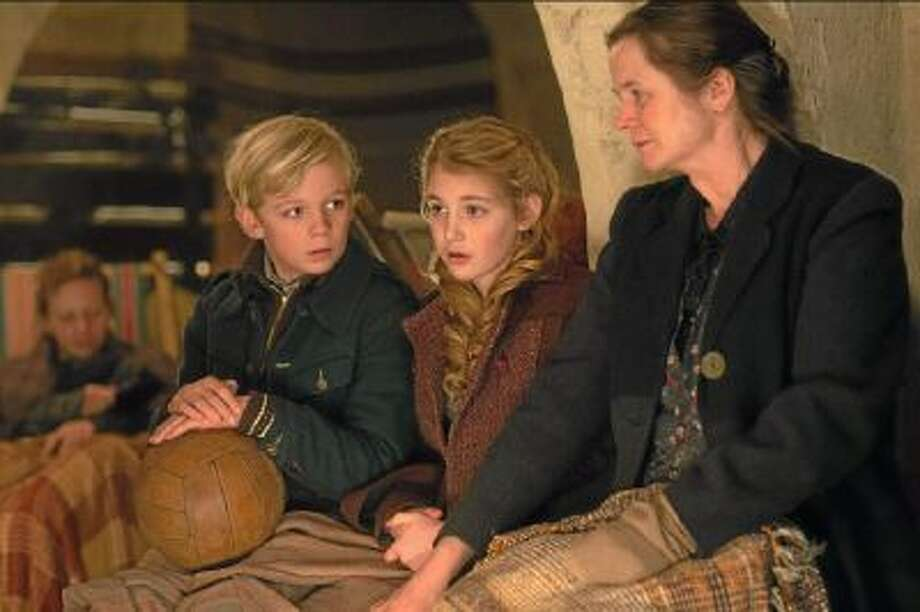 """This image released by 20th Century Fox shows Nico Liersch, from left, Sophie NÈlisse, and Emily Watson in a scene from """"The Book Thief,"""" about a girl who loves books."""