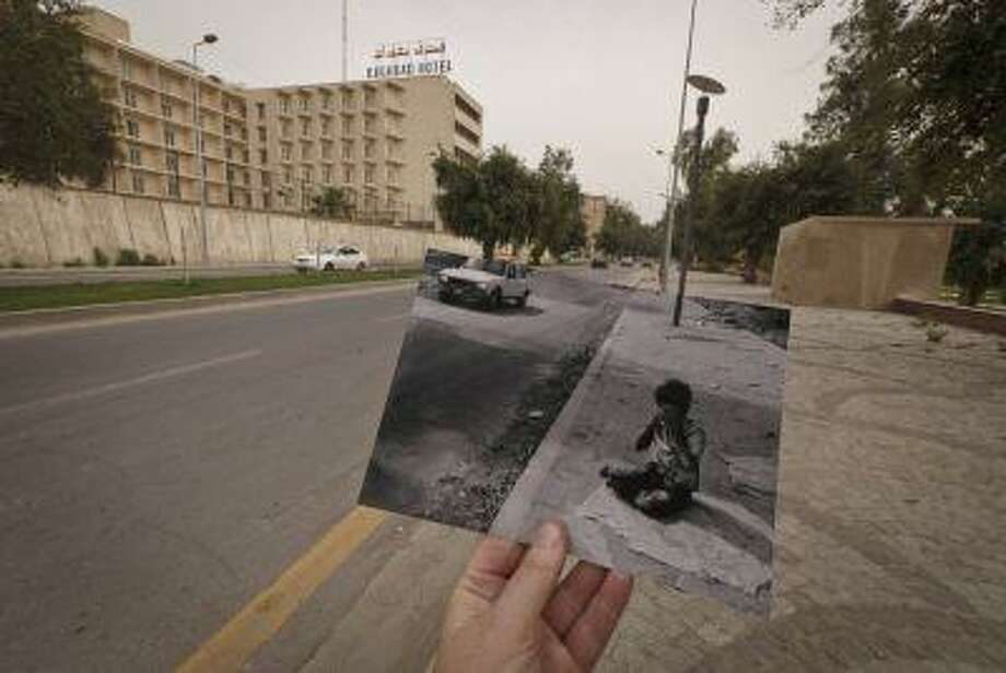 This March 12 photo shows a general view of Abu Nawas Street in Baghdad, Iraq, at the site of a photograph of Iraqi orphan Fady al-Sadik waking on the street, taken by photographer Maya Alleruzzo in April, 2003. The park that runs along Abu Nawas Street, named for an Arabic poet, is now a popular destination for families who are drawn by the manicured gardens, playgrounds and restaurants famous for a fish called mazgouf. Ten years ago, the park was home to a tribe of children orphaned by the war and was rife with crime. Photo: ASSOCIATED PRESS / AP2013