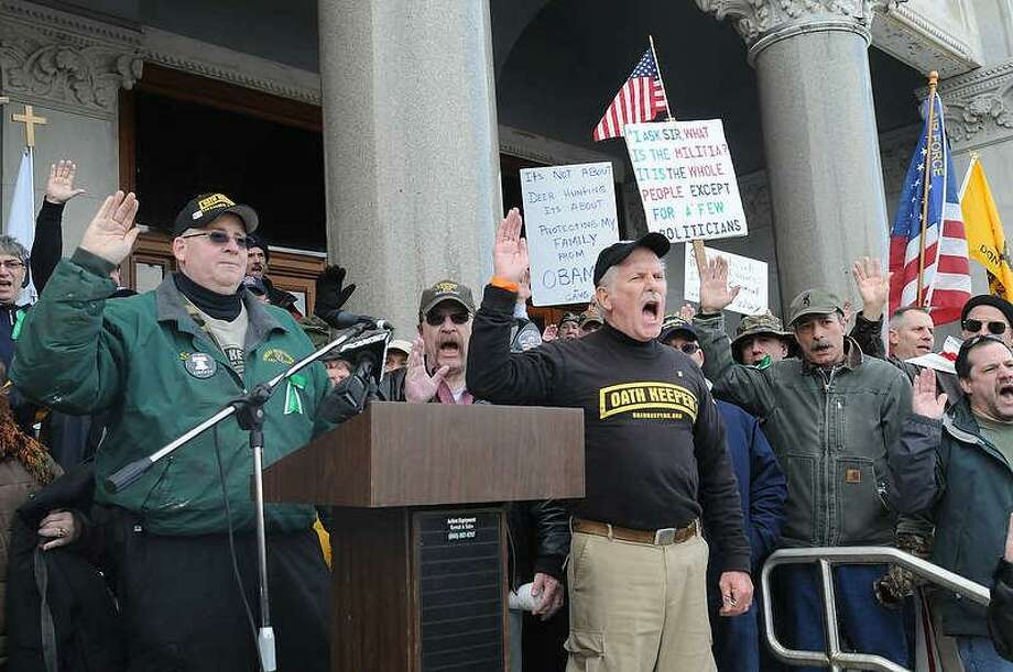 Firearms advocates take the Constitutional Oath lead by Oath Keepers Connecticut Chapter president John Beidler of Southington, Conn., at right of podium, as they  demonstrate on the steps of the state Capitol in Hartford during the first national Guns Across America Rally  and Gun Appreciation Day SaturdayJanuary 19, 2013. Photo by Peter Hvizdak / New Haven Register Photo: New Haven Register / ©Peter Hvizdak /  New Haven Register