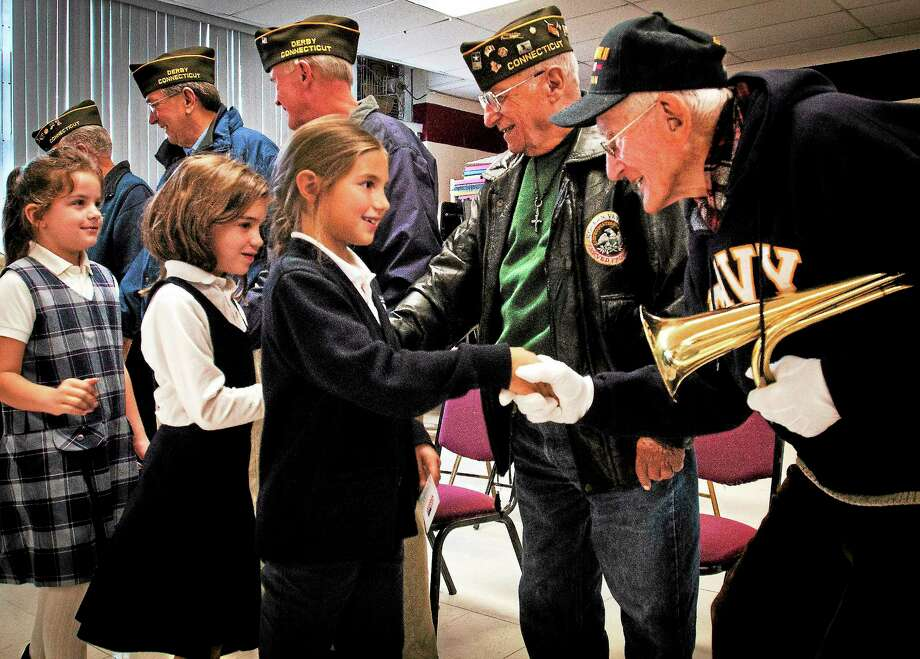 St. Mary-St. Michael School third grader Selena Hescock shakes hands with World War II Navy veteran Daniel R. Waleski after Veterans Day observances at the school Friday in Derby. Photo: Melanie Stengel — New Haven Register
