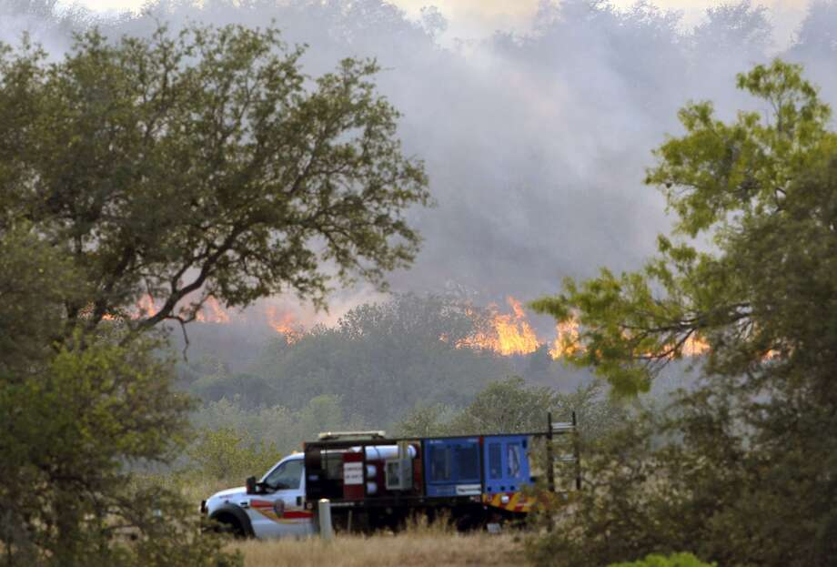 Firefighters work ahead of flames at a wildfire near Potranco Road and FM 211 in western Bexar County in September 2011. Bexar County commissioners approved a burn ban in the county Tuesday for the first time in a year because of the continuing dry conditions; there has been an average of 100 wildfires a month since January. Photo: TOM REEL /SAN ANTONIO EXPRESS-NEWS / ¨ 2011 San Antonio Express-News