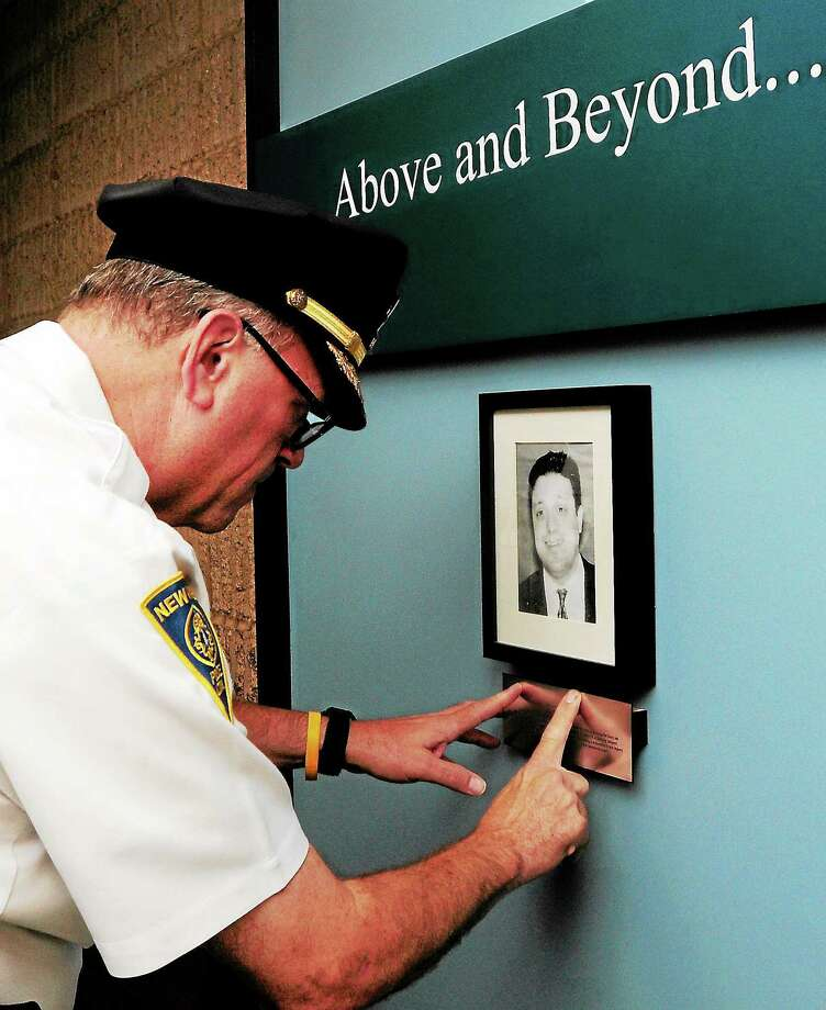(Peter Hvizdak — Register)New Haven Police Chief Dean Esserman looks closely at a plaque honoring  deceased NHPD Detective Andrew Faggio Tuesday, September 3, 2013 on a  new NHPD memorial wall before the start of a ceremony memorializing Faggio at police headquarters. Photo: New Haven Register / ©Peter Hvizdak /  New Haven Register