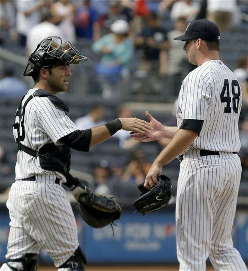 New York Yankees catcher Austin Romine, left, shakes hands with relief pitcher Boone Logan after defeating the Kansas City Royals in a baseball game at Yankee Stadium, Thursday, July 11, 2013, in New York. The Yankees won 8-4. (AP Photo/Seth Wenig) Photo: AP / AP
