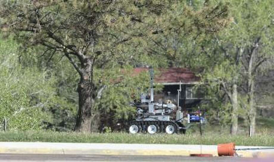 Boulder County Bomb Squad's robot checks a suspicious package next to parking lot at Fairview High School in Boulder, Colo., May 20, 2013. Photo: DAILY CAMERA / DAILY CAMERA