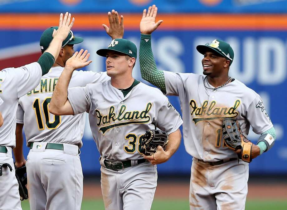 NEW YORK, NY - JULY 23:  Jaycob Brugman #28 and Rajai Davis #11 of the Oakland Athletics celebrate the 3-2 win over the New York Mets on July 23, 2017 at Citi Field in the Flushing neighborhood of the Queens borough of New York City.  (Photo by Elsa/Getty Images) Photo: Elsa, Getty Images