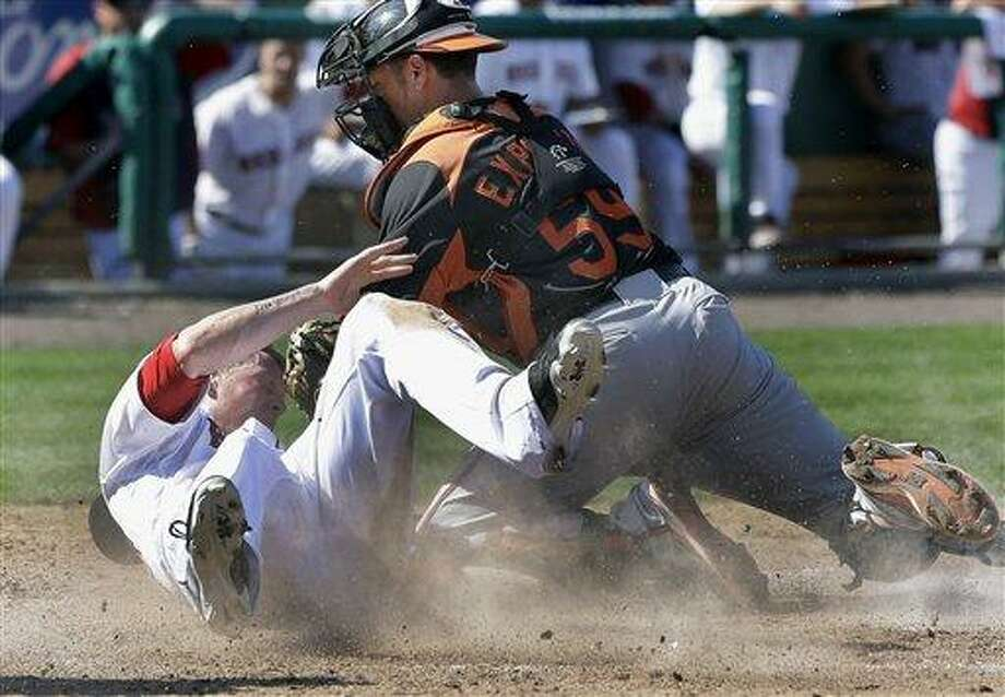 Boston Red Sox's Jeremy Hazelbaker slides safely into home to score on a single by Jonathan Diaz as Baltimore Orioles catcher Luis Exposito puts the tag on in the eighth inning of an exhibition spring training baseball game in Fort Myers, Fla., Tuesday, March 19, 2013. (AP Photo/Elise Amendola) Photo: ASSOCIATED PRESS / AP2013