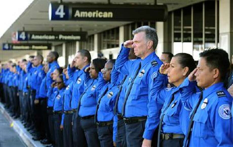 A long line of Transportation Security Administration personnel salute the U.S. Honor Flag procession Wednesday as it leaves Los Angeles International Airport in memory of TSA agent Gerardo Hernandez, who was killed by a rampaging gunman. Photo: ASSOCIATED PRESS / AP2013