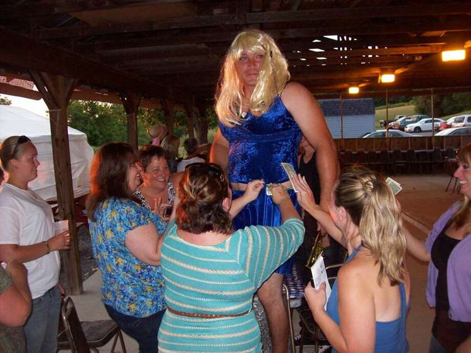 "Photo Special to the Dispatch by MIKE JAQUAYS Mike ""Michelle Lacey"" LaLonde receives tips from appreciative fansafter an athletic Legion Ladies runway strut that took him walking on top of tables and hanging from the rafters at the Munnsville American Legion on July 20, 2012."