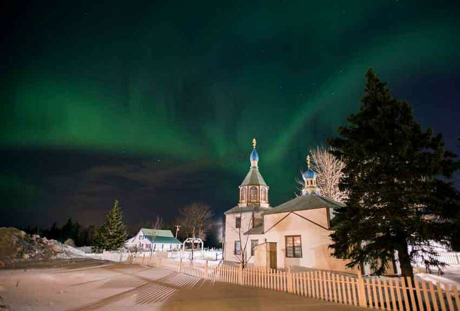 The aurora borealis, or northern lights, fill the sky early Sunday, March 17, 2013, above the Holy Assumption of the Virgin Mary Russian Orthodox church in Kenai, Alaska. The bright display at times filled the sky. (AP Photo/M. Scott Moon) Photo: ASSOCIATED PRESS / AP2013