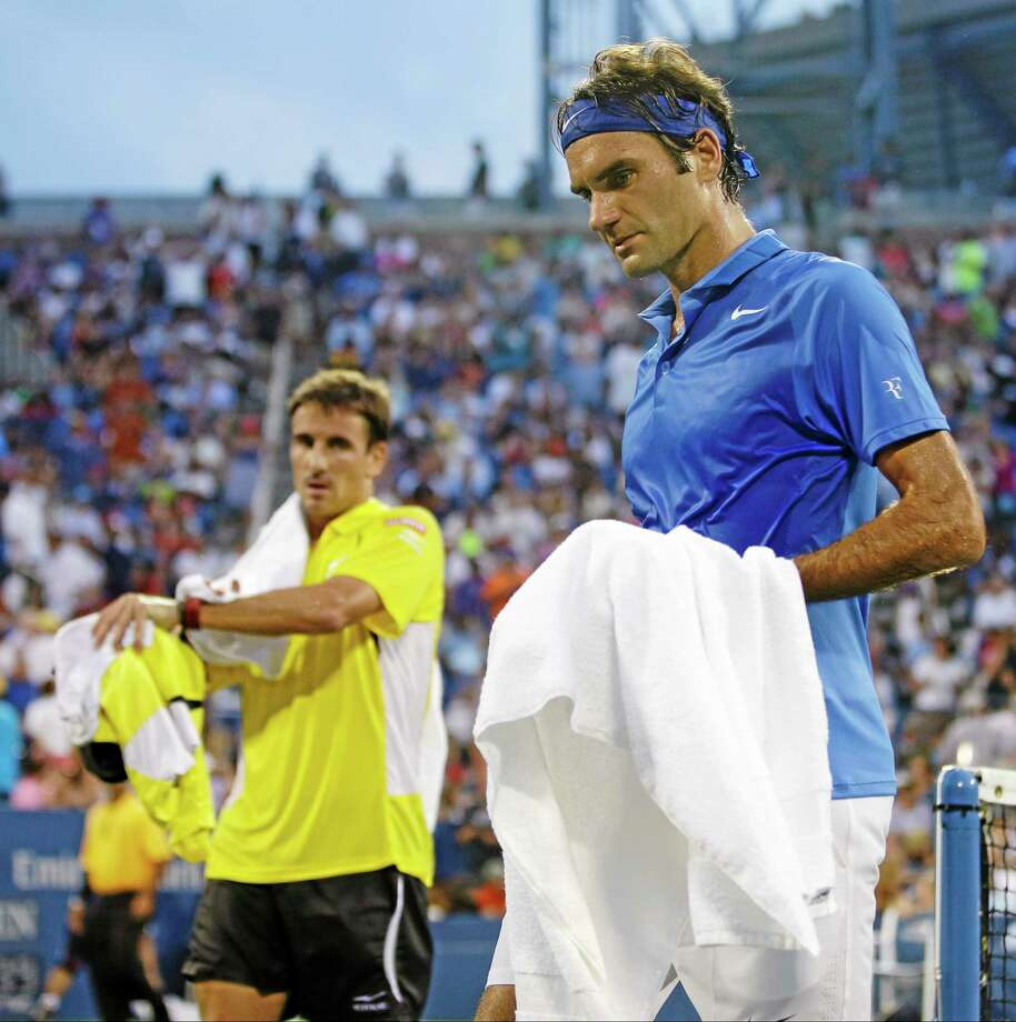 Roger Federer right, and Tommy Robredo walk off the court during a break in play during the fourth round of the U.S. Open Monday in New York. Photo: Darron Cummings — The Associated Press   / AP