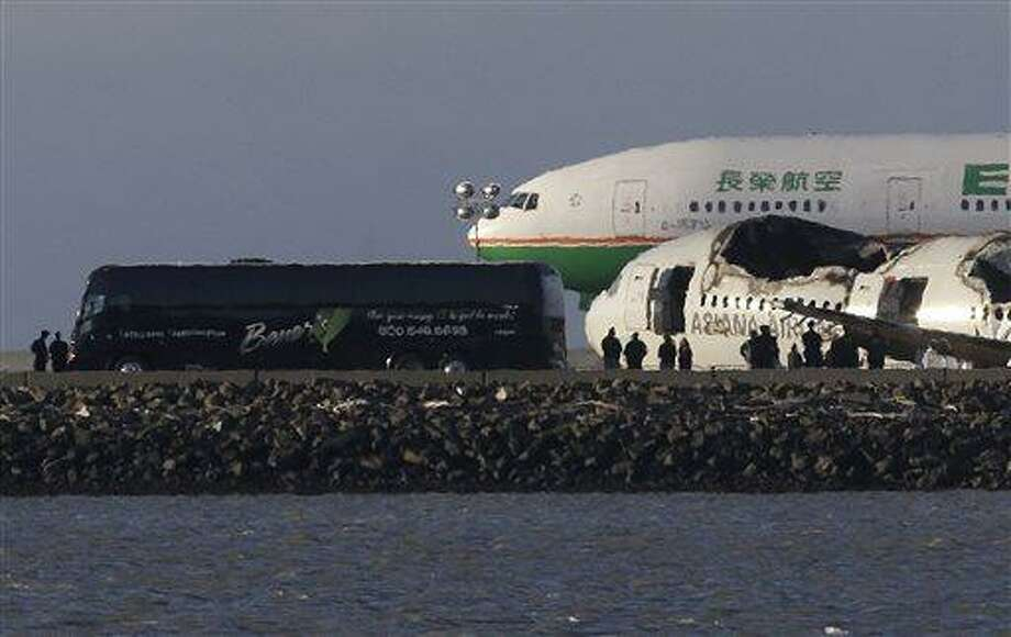 A group of people stand in front of the wreckage of Asiana Flight 214, which crashed on Saturday, July 6, 2013, as one of three buses that were reported to be carrying passengers and family members are parked next to it on a tarmac at San Francisco International Airport in San Francisco, Wednesday, July 10, 2013. Two passengers were killed and many others were injured in the crash. (AP Photo/Jeff Chiu) Photo: AP / AP