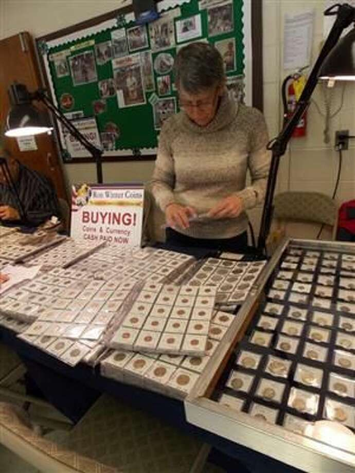 """A woman visits a recent coin show in New York. Debate has resurfaced on rather """"In God We Trust"""" should appear on US currency."""