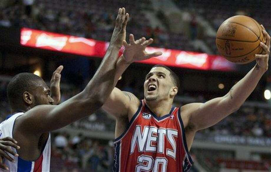 New Jersey Nets' Jordan Williams (20) goes to the basket against Detroit Pistons' Jason Maxiell in the first half of an NBA basketball game Friday, Feb. 10, 2012, in Auburn Hills, Mich. (AP Photo/Duane Burleson) Photo: ASSOCIATED PRESS / AP2012