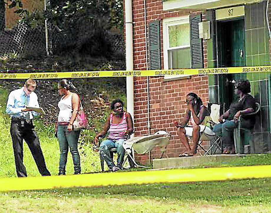 Peter Hvizdak/New Haven Register A New Haven Police detective talks to neighbors at 87 South Genesee Street as police investigate the scene of a shooting murder Wednesday afternoon July 3, 2013 near 85 South Genesee Street in New Haven. Photo: Journal Register Co.