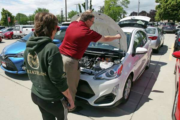 In this Tuesday, June 13, 2017, photo, Mark Miller Toyota salesman Doug Lund shows the engine of a Prius C Hybrid to shopper Mary Jean Jones, in Salt Lake City. The Conference Board releases its July index on U.S. consumer confidence, Tuesday, July 25, 2017. (AP Photo/Rick Bowmer)