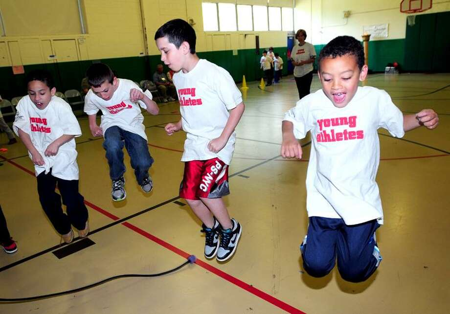 Left to right, David Lovelace, 9, Jake Cook, 10, Lucas Corrigan, 11, and Elijah Montgomery, 7, jump over a rope as part of the Young Athletes Program awards ceremony at Bradley School in Derby on 5/14/2013.Photo by Arnold Gold/New Haven Register   AG0497B