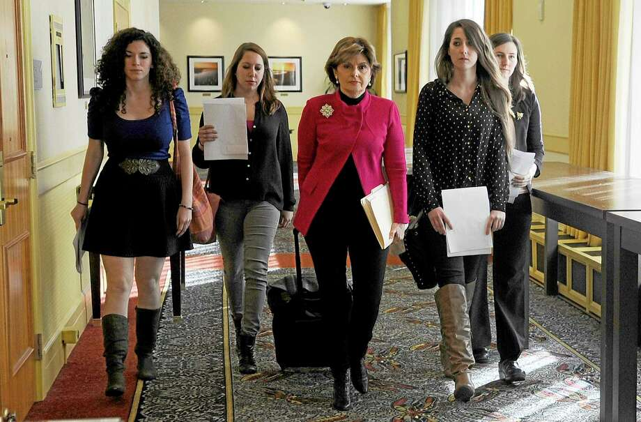 Attorney Gloria Allred, center, walks with University of Connecticut students Rose Richi, left, Erica Daniels, Carolyn Luby, second from right, and Kylie Angell, right, to a news conference in Monday, Oct. 21, 2013, in Hartford, Conn. Four women who say they were victims of sexual assaults while students at the University of Connecticut have announced they are filing a federal discrimination lawsuit against the school. (AP Photo/Jessica Hill) Photo: AP / FR125654 AP