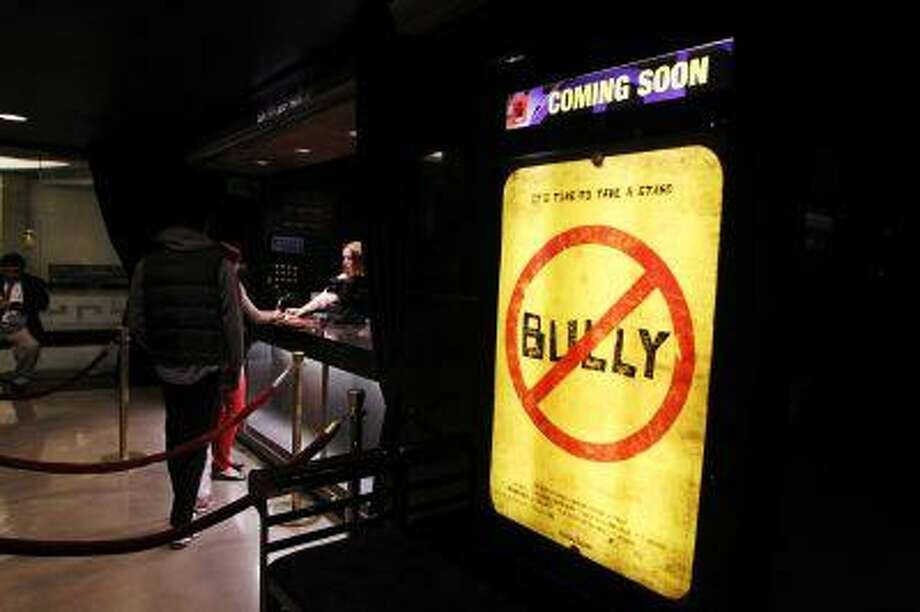 "People stand at the box office as a movie poster is seen for the documentary film ""Bully"" during its Los Angeles premiere in Hollywood, Calif. (Reuters/Danny Moloshok) Photo: REUTERS / X01907"