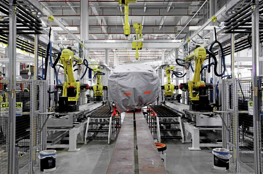 Paul Sancya — The Associated Press file photo          A covered vehicle sits in part of the new paint shop at Chrysler's Sterling Heights Assembly Plant in Sterling Heights, Mich. Photo: AP / AP
