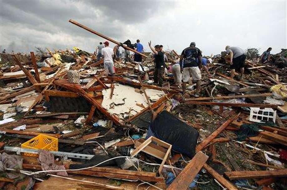 Workers look for victims under debris from a tornado that passed across south Oklahoma City, Monday, May 20, 2013. A monstrous tornado roared through the Oklahoma City suburbs, flattening entire neighborhoods with winds up to 200 mph, setting buildings on fire and landing a direct blow on an elementary school. (AP Photo/The Oklahoman, Paul Hellstern) Photo: AP / The Oklahoman