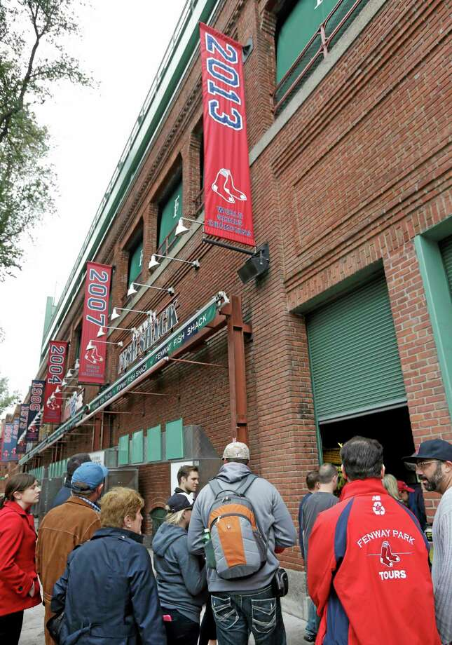 A tour group enters Fenway Park in Boston on Thursday under a 2013 World Series champions banner. The Red Sox defeated the St. Louis Cardinals 6-1 in Game 6 of the World Series on Wednesday to win the series. Photo: Steven Senne — The Associated Press   / AP