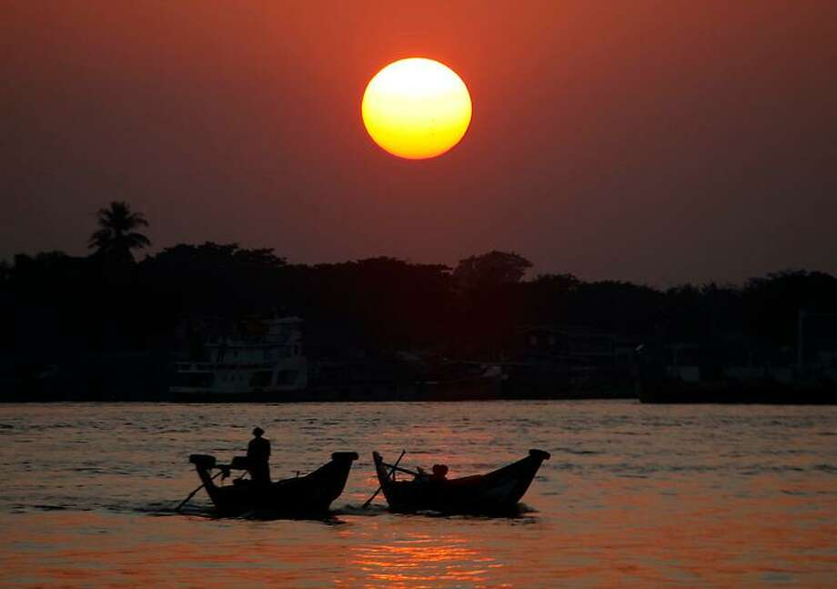 In this photo taken on Wednesday, Jan. 16, 2013, two boatmen cross the Yangon River to a jetty to carry passengers in Yangon, Myanmar. (AP Photo/Khin Maung Win) Photo: ASSOCIATED PRESS / AP2013